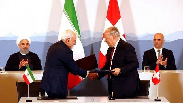 محمد جواد ظریف وزیر خارجهی ایران، چپ، و یوهان اشنایدر- امان وزیر اقتصاد سوئیس پس از امضای معاهدهای در برن با یکدیگر دست میدهند، ۳ ژوئیهی ۲۰۱۸.   (AFP Photo/Ruben Sprich)