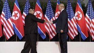 توضیح تصویر: دونالد ترامپ رئیس جمهور ایالات متحده، راست، در شهر تفریحی کاپلا، جزیرهی سنتوسا، دست خود را برای دستدادن با کیم یونگ اون رهبر کرهی شمالی دراز کرده است، سنگاپور، ۱۲ ژوئن ۲۰۱۸.  (AP Photo/Evan Vucci)