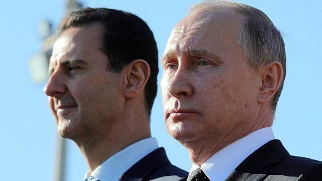 توضیح تصویر: در عکسی از 11 دسامبر 2017، ولادیمیر پوتین رئیس جمهور روسیه، راست، و بشار اسد رئیس جمهور سوریه از لشکریان در پایگاه هوایی حمیمیم در سوریه، سان می بینند.  (Mikhail Klimentyev, Sputnik, Kremlin Pool Photo via AP)