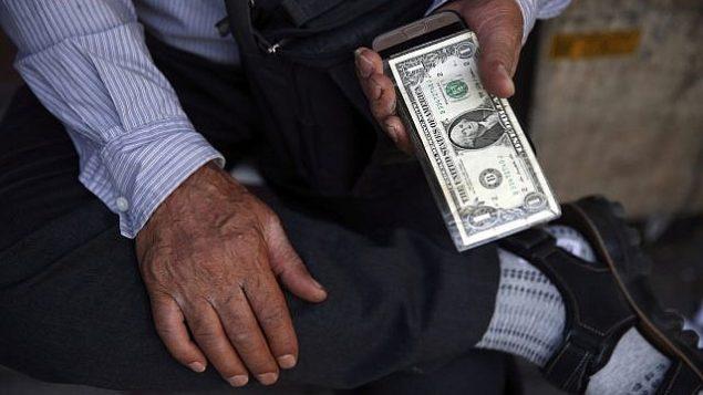 توضیح تصویر: یک فروشنده خیابانی ارز در ایران، در مرکز شهر تهران، اسکناس ایالات متحده را در دست دارد، تهران، ایران، 30 ژوئن 2018. (AP Photo/Vahid Salemi)