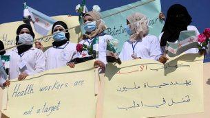 تصویر: کارکنان بخش های درمانی سوریه با پارچه-نگاری هایی در دست، حین راهپیمایی در روستای آتمه در شمال استان ادلیب، خاهان محافظت از بیمارستان در صورت وقوع حمله آتی شدند، ۱۶ سپتامبر ۲۰۱۸.  (AFP PHOTO / OMAR HAJ KADOUR)