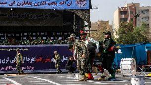 در عکسی از ۲۲ سپتامبر ۲۰۱۸ در اهواز، جنوب غرب ایران، سربازان ایرانی در حال خروج زخمی ها از صحنه پس از حمله به رژه ارتش در سالگرد آغاز جنگ ویرانگر با صدام حسین عراقی ۱۹۸۰ تا ۱۹۸۸. (AFP/ ISNA / MORTEZA JABERIAN)