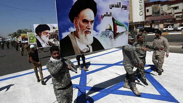 تصویر: در عکسی از ۲۳ ژوئن ۲۰۱۷، حامیان لشکر حزب الله عراق، که تحت حمایت ایران است، با تصویری از رهبر فقید ایران آیت الله خمینی و ولی فقیه ایران آیت الله علی خامنه ای، در بغداد، عراق، از روی پرچم اسرائیل رژه می روند. (AP/Hadi Mizban)