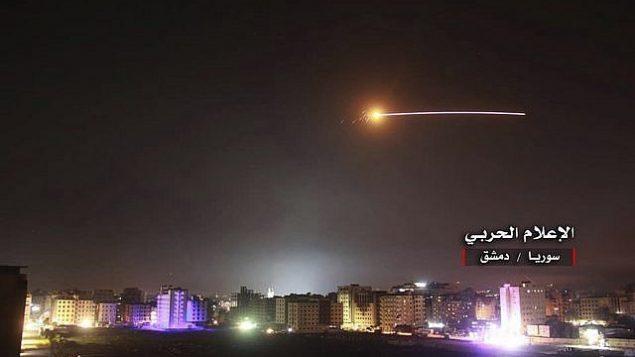 تصویر: در پی آن حمله انبوهی از راکت ها که ارتش اسرائیل متعلق به ایران می داند، به مواضع اسرائیل در بلندی های جولان، موشک های اسرائیلی مواضع دفاع هوایی و دیگر پایگاه نظامی در اطراف دمشق را زدند، و آتش ضد هوایی ها در ۱۰ مه ۲۰۱۸ به هوا بلند شده است. (Syrian Central Military Media, via AP)