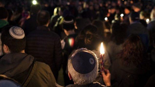 تصویر: مردم در خیابانی در محله اسکویر هیل پیتزبورگ، جایی که یک تیرانداز طی مراسم مذهبی کنیسای درخت زندگی به روی حاضران آتش گشود، شنبه ۲۷ اکتبر ۲۰۱۸. (AP/Keith Srakocic)