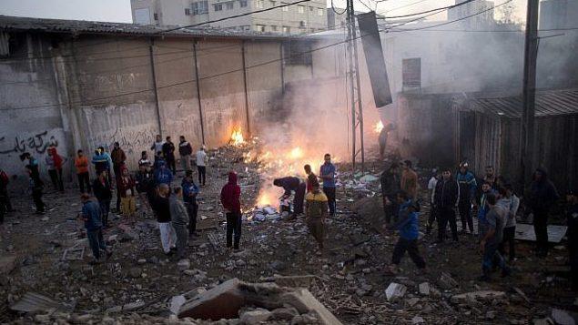 تصویر: فلسطینی ها ابعاد تخریب ساختمان هایی که در پی حمله هوایی اسرائیل در پاسخ به هجوم راکت ها از شهر غزه، منهدم شدند را وارسی می کنند، ۲۷ اکتبر ۲۰۱۸. (AP Photo/Khalil Hamra)