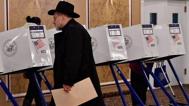 تصویر: یکی از رأی دهندگان رأی خود را در در حوزه رأیگیری مرکز یهودیان در مید-وود شرقی در بروکلین بوروی شهر نیویورک به صندوق می اندازد، ۶ نوامبر ۲۰۱۸. (Angela Weiss / AFP)