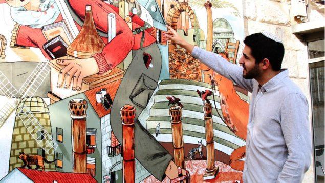 تصویر: ریو راویتزکی، شاعر و نمایشنامه نویس، خالق زنجیره آثار هنری «گپ و گفت خیابانی» در مقابل دیوارنگاری بر خیابان غزه در اورشلیم. (Shmuel Bar-Am)