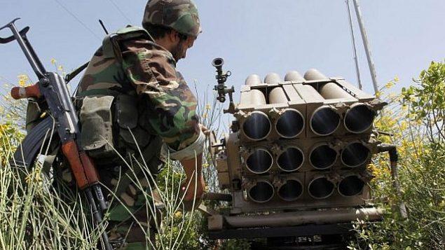 تصویر: یک پیکارگر حزب الله ایستاده پشت یک پرتابگر خالی راکت، ۲۲ مه ۲۰۱۰. (AP/Hussein Malla)