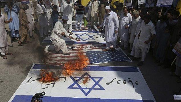 تصویر: مسلمانان شیعی پرچم های اسرائیل و ایالات متحده را در راهپیمایی روز قدس (اورشلیم) در پیشاور پاکستان به آتش می کشند، جمعه ۲۳ ژوئن ۲۰۱۷. (AP Photo/Muhammad Sajjad)