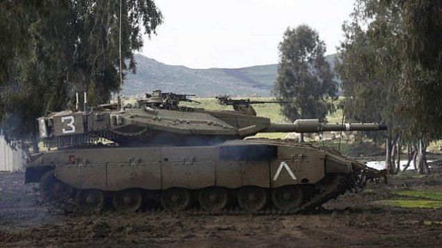 تصویر: یک تانک اسرائیلی مرکاوا حین شرکت در مانور نظامی در ناحیه منضم به اسرائیل بلندی های جولان، ۱۲ فوریه ۲۰۱۹. (Photo by JALAA MAREY / AFP)