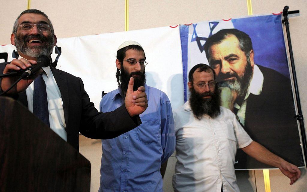 تصویر: مایکل بن آری، چپ، حین گفتگو در مراسم بزرگداشت رهبر افراطی یهودی، مئر کاهانی، خاخام متوفا در سالنی در اورشلیم، ۲۶ اکتبر ۲۰۱۰. در سمت راست، باروخ مارزل ایستاده است. (Yossi Zamir / Flash 90)