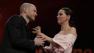 تصویر: نداو لاپید، فیلمساز، چپ، حین دریافت خرس طلایی برلیناله برای آخرین فیلم خود، «هم-معناها». (Courtesy PR)