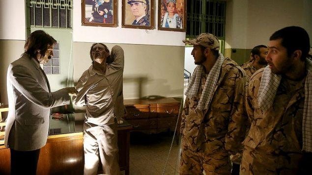 سربازان سپاه پاسداران انقلاب اسلامی هنگام تماشای نمایشگاهی در یکی از زندان های سابق ساواک، سازمان امنیت و اطلاعات پیش از انقلاب، در مرکز شهر تهران، ایران، که اکنون تبدیل به موزه شده، و مجسمه های مومی از بازجو و زندانی در حال شکنجه به نمایش گذاشته شده است. پرتره هایی از شاه، شهبانو فرح، و پسر ایشان ولیعهد رضا پهلوی که اکنون در ایالات متحده در تبعید به سر می برد، بالای صحنه آویخته است، ۷ ژانویه ۲۰۱۹.  (AP Photo/Ebrahim Noroozi)