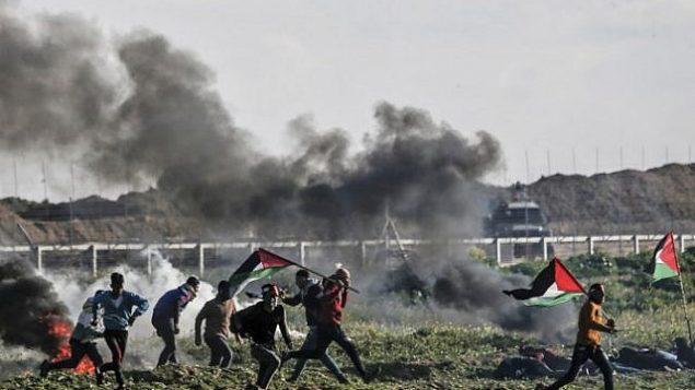 تصویر: فلسطینی ها، در درگیری های نزدیک حصار امنیتی مرزی اسرائیلی، شرق شهر غزه، با پرچم فلسطینی از برابر لاستیک های آتش زده می گذرند، ۲۲ فوریه ۲۰۱۹. (Mahmud Hams/AFP)