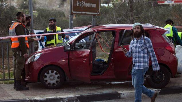تصویر: کارکنان پزشکی قانونی اسرائیل اتوموبیلی در حوالی محل حمله در نزدیکی تقاطع آریل در کرانه باختری را مورد تجسس قرار داده اند، ۱۷ مارس ۲۰۱۹. (JAAFAR ASHTIYEH / AFP)