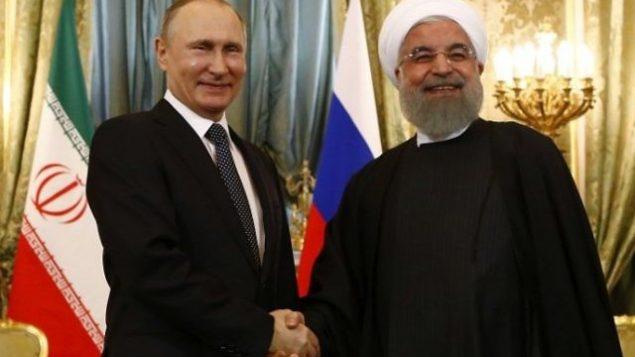 تصویر: ولادیمیر پوتین رئیس جمهور روسیه، چپ، حین دست دادن با همتای ایرانی خود حسن روحانی طی ملاقات ایندو در مسکو، ۲۸ مارس ۲۰۱۷. (Sergei Karpukhin/AFP)