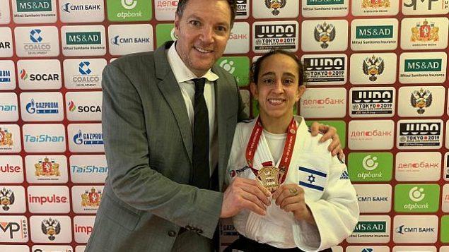 گیلی کوهن جودکار اسرائیلی، راست، پس از گرفتن مدال طلا در مسابقات بزرگ در اکاترینبورگ، روسیه، با مربی خود شانی هرسکو در مقابل دوربین ایستاده است، ۱۵ مارس ۲۰۱۹. (Israel Judo Association)