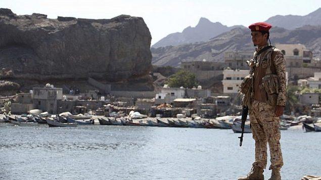 سربازی از متحدان دولت به رسمیت شناخته شدهٔ بین المللی یمن در بازار ماهی فروشان، در عدن، یمن، به نگهبانی ایستاده است، پنجشنبه ۱۳ دسامبر ۲۰۱۸. (AP Photo/Jon Gambrell)
