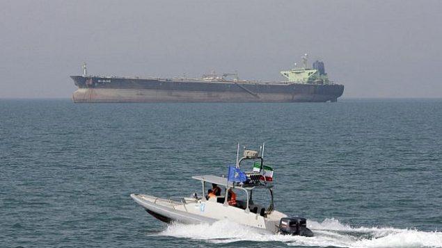 در عکسی از ۲ ژوئیه ۲۰۱۲، یک قایق موتوری سپاه پاسداران انقلاب ایران در آبهای خلیج فارس می راند و یک تانکر نفت نیز در پسزمینه دیده می شود. (AP Photo/Vahid Salemi)