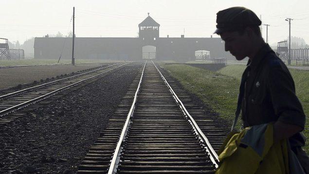در عکسی از ۲۹ ژوئیه ۲۰۱۶، مردی از ریل معروف که به اردوگاه مرگ پیشین نازی در آشویتس-بیرکنا در لهستان منتهی می شود، می گذرد