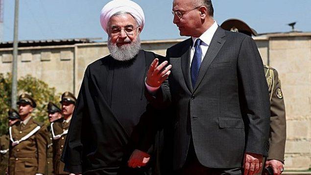 برهام صالح رئیس جمهور عراق، راست، پس از بازدید از یک گارد افتخار در قصر سلام، بغداد، ۱۱ مارس ۲۰۱۹،  در کنار حسن روحانی رئیس جمهور ایران گام برمی دارد. (AP Photo/Khalid Mohammed)