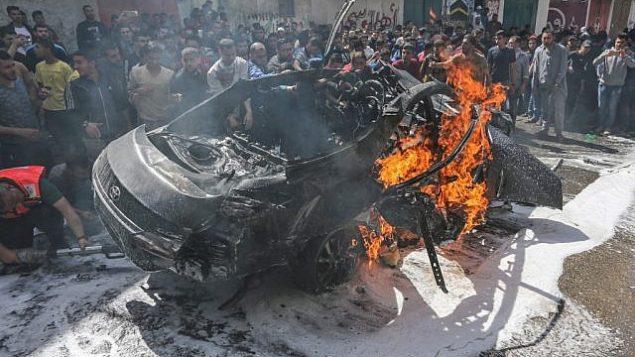 تصویر: کارکنان اورژانس فلسطینی می کوشند شعله های آتش اتوموبیل متعلق به حامد الخوداری فرمانده ارشد حماس، پس از آن که در ۵ می ۲۰۱۹ مورد اصابت حمله هوایی اسرائیل قرار گرفت را فرو بنشانند.  (MAHMUD HAMS / AFP)