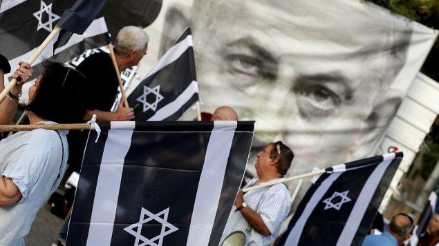 تصویر: اسرائیلیها، پرچم به-دست، در راهپیمایی علیه بنیامین نتانیاهو نخست وزیر، ۲۵ مه ۲۰۱۹، تل آویو.  (JACK GUEZ / AFP)