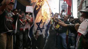 تصویر: پنجشنبه ۸ ژانویه ۲۰۰۹، تظاهرکنندگان در مقابل سفارت اسرائیل در کاراکاس، پرچم اسرائیل را به آتش می کشند. معترضین به حمله اسرائیل به نوار غزه، روز پنجشنبه گرافیتی اسپری کردند و به سمت سفارت کشور در ونزوئلا لنگه کفش پرتاب کردند و از تصمیم هوگو چاوز رئیس جمهور در اخراج سفیر اسرائیل حمایت کردند.  (AP Photo/Fernando Llano)