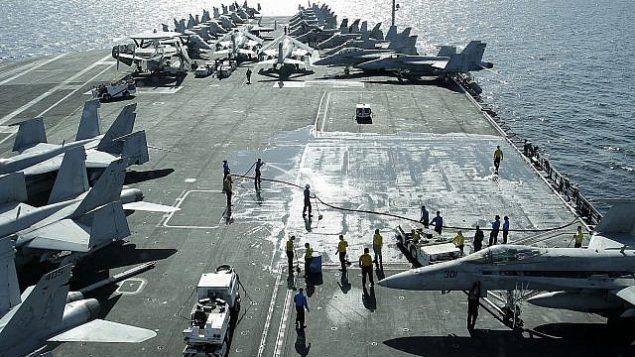 تزئینی – منظره ای از روی پل از ناو هواپیما نیمیتز-کلاس کشتی آبراهام لینکلن ایالات متحده (سی وی ان ۷۲) جت های ایالات متحده را نشان می دهد که بر عرشه پرواز، در تنگه هرمز بیرون از خلیج ایران پارک شده اند، ۱۵ فوریه ۲۰۱۲. (AP /Hassan Ammar)