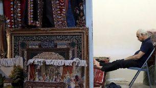 تصویر: یک قالی فروش در بازار قدیم تهران، تهران، ۲۳ ژوئن ۲۱۹. (AP Photo/Ebrahim Noroozi)