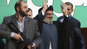 در عکسی از ۱۷ سپتامبر ۲۰۱۲، «حسن نصرالله» رهبر حزب الله، وسط، در میان بادیگاردهای خود، برای جمعیت دههاهزار نفری حامیان در راهپیمایی بیروت، لبنان، دست تکان میدهد. (AP Photo/Hussein Malla, File)