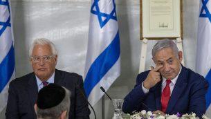 تصویر: ۱۶ ژوئن ۲۰۱۹، در مراسمی معرفی شهرک تازه ای به نام دونالد ترامپ رئیس جمهور ایالات متحده به عنوان تقدیر از اقدام وی به شناسایی حاکمیت اسرائیل بر بلندیهای جولان، بنیامین نتانیاهو نخست وزیر اسرائیل کابینه خود را با حضور دیوید فریدمن سفیر ایالات متحده برگزار میکند. (AP/Ariel Schalit)