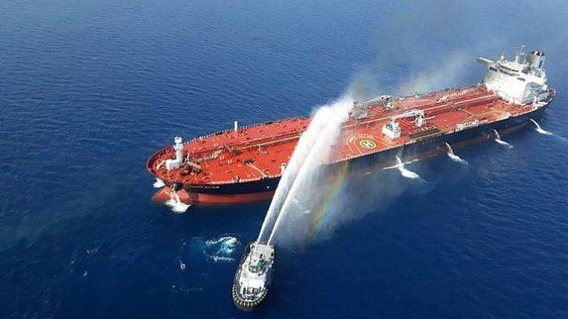 تصویر: قایق نیروی دریایی ایران برای فرونشاندن آتش نفتکش دریای عمان آب میپاشد، پنجشنبه ۱۳ ژوئن ۲۰۱۹.  (AP Photo/Tasnim News Agency)