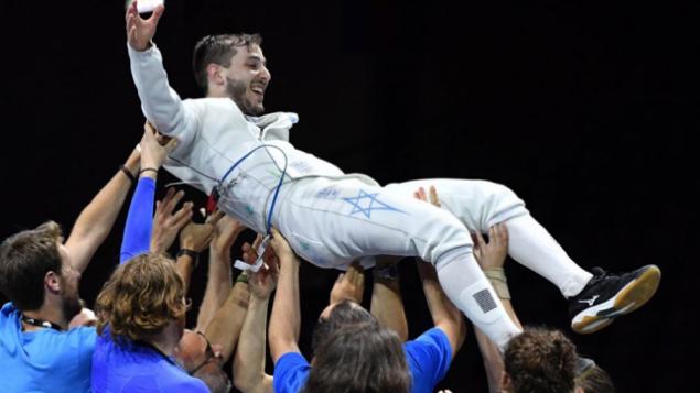 تصویر: «یووال فریلیخ» را تیم او در پس از برنده ندال طلای مسابقات قهرمانی شمشیربازی دوسلدورف، ۱۸ ژوئن ۲۰۱۹، روی دست بلند کرده اند. (Facebook photo/ European Fencing Confederation)