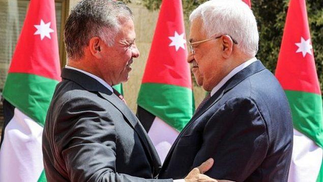تصویر: محمود عباس رئیس تشکیلات خودگردان فلسطینی، راست، شاه عبدالله دوم را هنگامی که برای استقبال از وی در کاخ سلطنتی در عمان، پایتخت، وارد میشود، در آغوش میگیرد، ۸ اوت ۲۰۱۸. (AFP/Pool/Khalil Mazraawi)