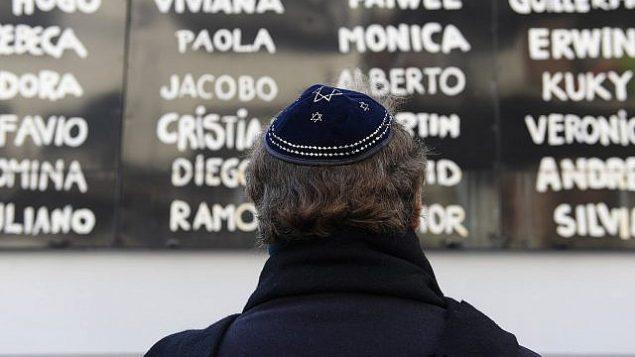 تصویر: مردی در مقابل مرکز فرهنگی یهودیان انجمن آرژانتین و اسرائیل (آمیا)، بوئنوس آیرس، ۱۸ ژوئیه ۲۰۱۷  در مراسم یادبود بیست و سومین سالگرد بمبگذاری تروریستی در محل که به کشته شدن ۸۵ تن و زخمی شدن ۳۰۰ تن دیگر از مردم منجر شد. (AFP / Juan Mabromata / Getty Images)