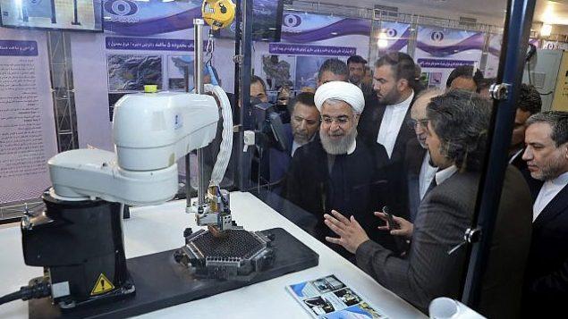 تصویر: در عکسی از ۹ آوریل ۲۰۱۸، که در وبسایت رسمی ریاست جمهوری ایران منتشر شد، حسن روحانی رئیس جمهور در مراسمی به مناسبت «روز ملی انرژی اتمی» در تهران، ایران، به توضیحاتی پیرامون دستاوردهای تازه هسته ای گوش فرا میدهد. (Iranian Presidency Office via AP, File)