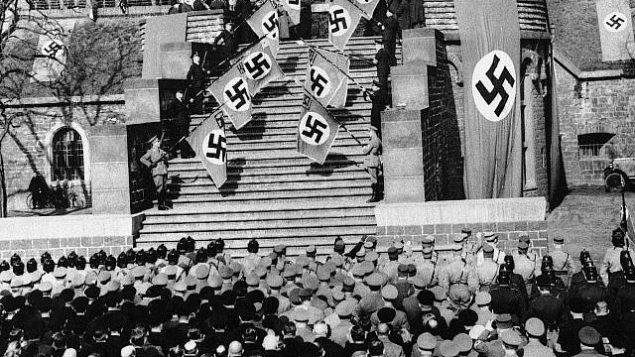 تصویر: منظره ای از مراسم افراشتن پرچم در پارک «هیندنبورگ»، کلن، آلمان، ۹ مارس ۱۹۳۶. واحد ویژه لشکر تهاجمی نازی نظامی-شدن دوباره راینلند آلمان و لغو معاهده ورسای را طی تظاهراتی  پرشور در هیندنبرگ، قدیمیترین قلعه راین، جشن میگیرند. این تظاهرات در رابطه با روز سوگواری ملی آلمان برگزار شد. (AP Photo)