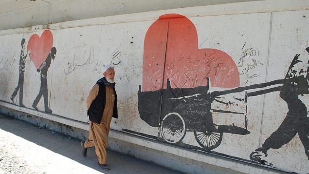 تصویر: مردی از اهالی افغانستان از کنار دیوارنگاره ای در نزدیکی محل بمباران مرگبار میگذرد که بر آن شعارهایی با مضمون «مرگ بر اسرائیل» نوشته شده. (Ezzatullah Mehrdad/ Times of Israel)