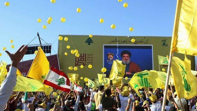 تصویر: حامیان گروه تروریستی حزب الله با پرچم گروه در دست، در تظاهرات سیزدهمین سالگرد پایان جنگ ۲۰۰۶ با اسرائیل در شهر جنوبی «بنت جبیل» لبنان، ۱۶ اوت ۲۰۱۹. (Mahmoud ZAYYAT / AFP)