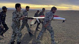 تصویر: در عکسی که در ۵ نوامبر ۲۰۱۸ از سوی ارتش ایران عرضه شد، در یکی از تمرینات نظامی در سمنان، ایران، سربازان در حال حمل قطعه ای از پهبادی که سقوط کرده دیده میشوند. (Iranian Army via AP)