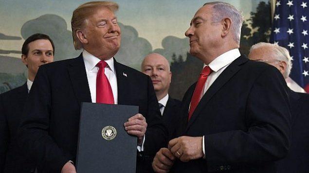 تصویر: دونالد ترامپ رئیس جمهور ایالات متحده، پس از امضای سند شناسایی حاکمیت اسرائیل بر بلندیهای جولان، در اتاق پذیرایی دیپلماتیک کاخ سفید، به بنیامین نتانیاهو نخست وزیر اسرائیل، راست، لبخند میزند، شهر واشنگتن، ۲۵ مارس ۲۰۱۹. (AP/Susan Walsh)