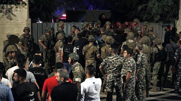 تصویر: نگبهانهای لبنانی در نزدیکی مکانی که گفته میشود پهبادهای اسرائیل به یکی از مقرهای گروه لبنانی حزب الله در محله ای در حومه جنوبی بیروت اصابت کرد ایستاده اند، ۲۵ اوت ۲۰۱۹. (AP/Bilal Hussein)