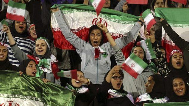 تصویر: زنان ایران در حال تشویق تیم، با پرچم ایران در دست، در عکسی از ۱۶ اکتبر ۲۰۱۸، هنگامی مقامات مسؤول در حرکتی کم-سابقه به زنان اجازه ورود به استادیوم آزادی و تماشای بازی دوستانه میان تیمهای فوتبال ایران و بولیوی را دادند، تهران، ایران. (AP Photo/Vahid Salemi, File)