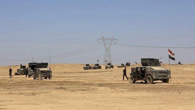 تصویر: نیروهای نخبه مقابله با تروریسم در عراق، حین پیشروی در مسیر شنی کویر، خارج شهر «هیت» که در تصرف داعش است و در ۸۵ مایلی (۱۴۰ کیلومتر) غرب بغداد، عراق، قرار دارد، یکشنبه ۳ آوریل ۲۰۱۶.  (AP/Khalid Mohammed)