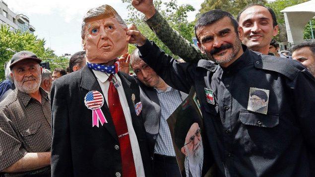 تصویر: تظاهرکنندگان ایرانی پوستری از علی خامنه ای ولی فقیه ایران و آدمک دونالد ترامپ رئیس جمهور ایالات متحده را در راهپیمایی ۱۰ مه ۲۰۱۹ در تهران حمل میکنند. (Stringer/AFP)