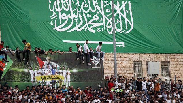 تصویر هواداران فوتبال در مسابقه مقدماتی جام جهانی ۲۰۲۲ آسیا میان فلسطینیها و عربستان سعودی، در شهر «الرام»، کرانه باختری، ۱۵ اکتبر ۲۰۱۹، زیر بانر عظیم پرچم ملی سعودی ایستاده اند.  (Ahmad GHARABLI/AFP)