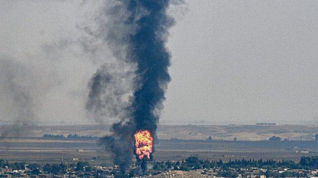 تصویر: در عکسی از ۱۷ اکتبر ۲۰۱۹ از سمت مرز ترکیه با سوریه در ناحیه «جیلان پینار» شهر «شانلی اورفا»، دود و آتشی که از شهر رأس العین سوریه بر اثر تهاجم ترکیه علیه مردم کورد در شمال شرقی سوریه بهوا خاسته را نشان میدهد. (Photo by Ozan KOSE / AFP)