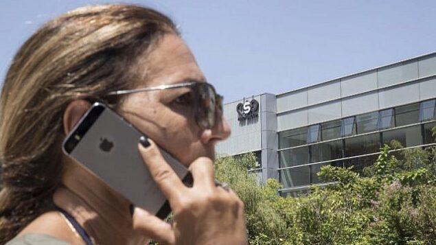 تصویر: یک زن اسرائیلی در حال استفاده آیفون خود در مقابل ساختمان شرکت امنیت سایبری اسرائیل «گروه ان.اس.او»، ۲۸ اوت ۲۰۱۶، هرتصلیه، نزدیک تل آویو. (AFP Photo/Jack Guez)
